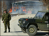 Kfor soldier stands near a burning customs post at Brjnak
