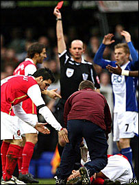 Referee Mike Dean shows a red card to Martin Taylor (out of shot) as Eduardo receives treatment