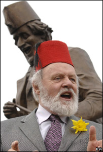 Sir Anthony wearing a fez in front of the Tommy Cooper statue