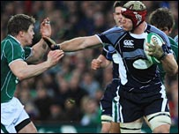 Brian O'Driscoll  is held off by Scotland's Alasdair Strokosch