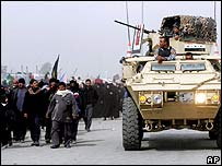 Iraqi army passes Shia pilgrims leaving Baghdad on their way to Karbala.