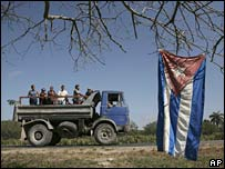 A Cuban flag hangs from a tree as Cubans ride on the back of a truck along the Santiago-Havana road