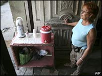 A woman sells  coffee from the doorway of her home in Havana