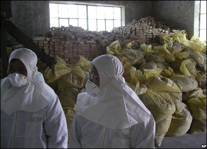 North Korean nuclear workers stand in front of insulating bricks and sand in the Yongbyon nuclear plant , North Korea (14/02/2008)