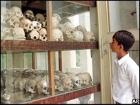 Cambodian people stand in front of a stall to watch victims skulls during a commemoration Day at a killing field in Choeung Ek