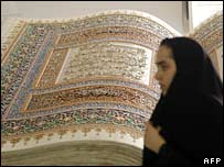 An Iranian woman walks past a large Koran