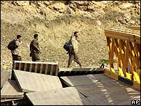 Unidentified armed Kurdish men pass a bridge used by the PKK in Iraq, destroyed by a Turkish air attack, on 24 February