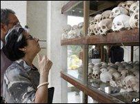 A visitor looks at human skulls at Tuol Sleng, Cambodia