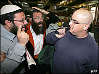 Omri Sharon (right) assailed by right-wing Jewish activists outside court