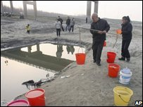 People fetch water from a pool next to Dongjing river in Hubei province, China 27/02/2008