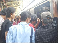 Commuters try to board packed train in Jakarta