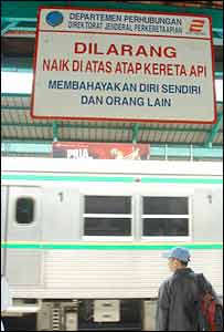 Sign in Jakarta railway station warning passengers not to go on roof of train