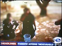 Screen grab from South Africa's ETV, allegedly showing black employees at a university being humiliated by white students