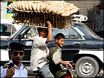 An Egyptian bread vendor carries a tray of bread on his head whilst cycling in a Cairo street