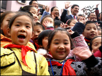 Chinese schoolgirls welcome David Miliband (background, right)