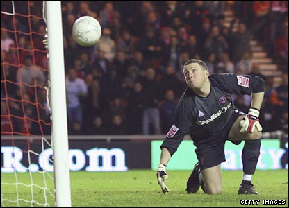 Paddy Kenny looks on as the ball rebounds into the net