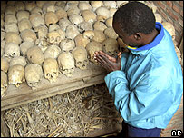 A Rwandan genocide survivor prays at the remains of victims at a mass grave in Nyamata, 2004.