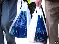 Shoppers with plastic bags exit Marks and Spencer