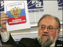 Russia's election chief Vladimir Churov holds an official election poster. File photo