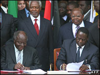 Kenyan President Mwai Kibaki (L) and opposition leader Raila Odinga sign the deal as Kofi Annan (back left) looks on, 28 February 2008