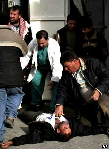 A Palestinian man falls unconscious after seeing the bodies of four Palestinian youths at the morgue of Kamal Edwan hospital in Beit Lahiya