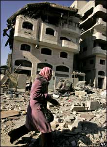 A Palestinian woman walks past the damaged Hamas-run interior ministry.