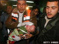 Paramédico palestino lleva a un niño herido durante un ataque israelí en Gaza