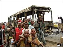 Children stand around a charred bus in Douala, Cameroon, on 24 February