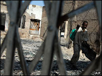 Boy walks through burnt-ourt shop
