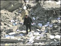 Policía palestino camina sobre escombros de edificio bombardeado en Gaza