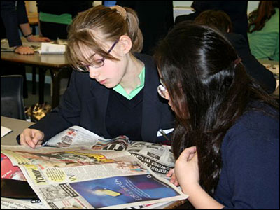 Guildford County School students studying a newspaper