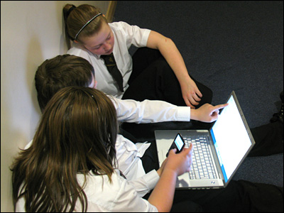 Three students from South Chadderton school using an MP3 player to record their script, while reading it off a laptop