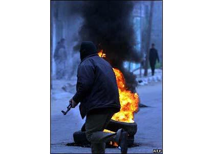 Hamas militant and burning tyre in Jabaliya refugee camp - photo 1 March