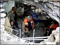 Israelis inspect a hole in the roof of a flat after it was it with a rocket fired in the coastal city of Ashkelon.