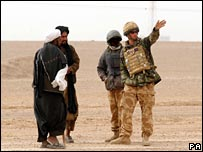 Prince Harry tells two Afghan men the route around an army cordon