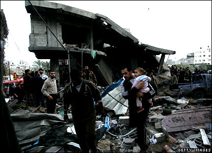 A Palestinian runs with a child as people inspect a destroyed house after an Israeli strike