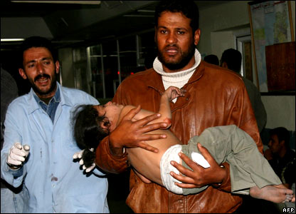 A Palestinian man carries a wounded girl into a hospital in Gaza City