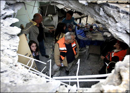 An Israeli rescue worker and residents are seen through a hole in the roof of an apartment after it was it with a rocket fired by Palestinian militants in Gaza, in the coastal city of Ashkelon