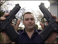 Ch Insp Trickey with two guns, one fake and one real