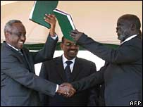 Sudan's Vice-president Ali Osman Taha, left, shakes hands with SPLM/A leader John Garang while exchanging copies of the final peace accord in Nairobi, Kenya, 9 January 2005