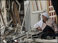 A woman sits outside a destroyed shop in Gaza