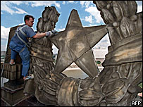 Municipal worker cleaning Soviet stars of the top of Ukraina Hotel in Moscow