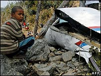 A boy sits beside the wreckage at the site of the UN crash