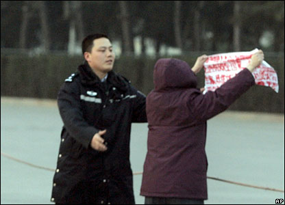 A Chinese police officer tries to stop a protester holding up a banner in front of journalists waiting to enter the Great Hall of the People