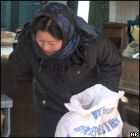 A woman collects international food aid in North Korea.