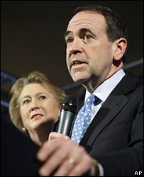 Mike Huckabee announces his withdrawal from the race, watched by wife Janet