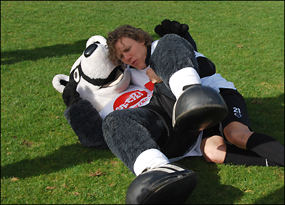 Fulham midfielder Jimmy Bullard grapples with the club's mascot Billy the badger