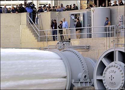 US Secretary of the Interior Dirk Kempthorne, in blue shirt at railing, watches water flow from the number one and two jet tubes at the Glen Canyon Dam