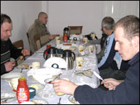Men eating a meal round a table
