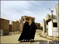 Two Iraqi women walk near a blast wall in the Karrada neighbourhood of Baghdad (archive)